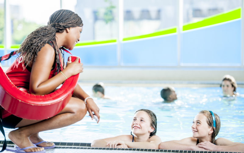 A group of children are swimming in an indoors pool at a fitness center. Two girls are resting at the side of the pool, and talking to the lifeguard.